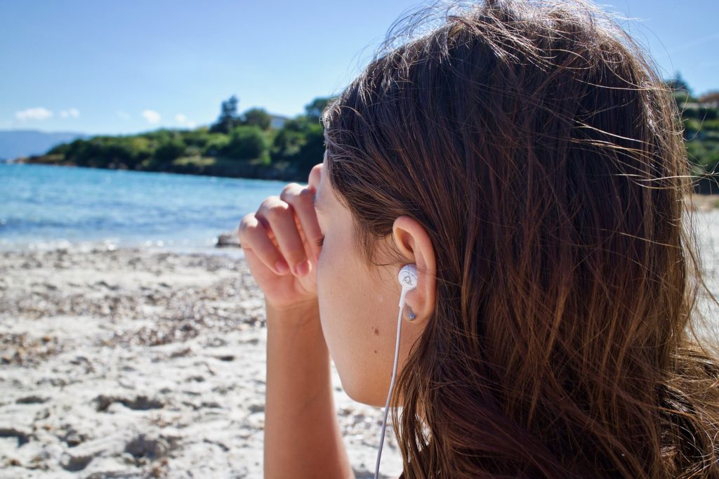 Photo of woman wearing earbuds staring out to sea